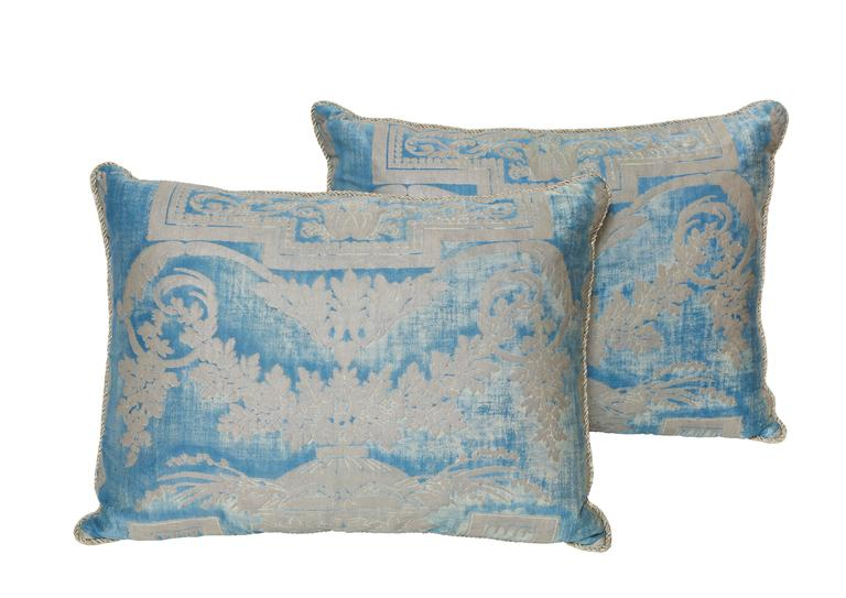 A set of three Fortuny silk pillow cushions in metallic blue and silver fabric depicting a neoclassical design with a draped garland motif, with braided trim and woven back