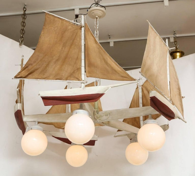 A sailboat form chandelier, the off-white painted wooden frame in the form of a propeller issuing five arms with affixed sailboat with linen mast, the underside of each arm suspending a globe Form Light, Edison socket, 40 watt maximum recommended.