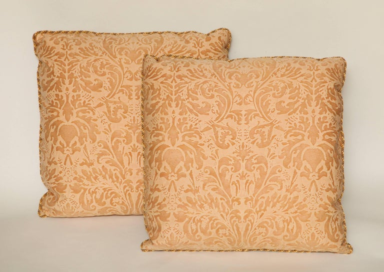 A pair of Fortuny fabric cushions in the Lucrezia pattern, apricot colorway with striped linen backing and braided trim, the pattern, a 17th century Italian motif named after Rembrandt's 1666 masterpiece, Lucretia