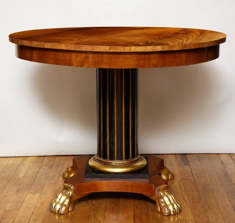 A Regency centre table, parcel gilt and ebonized fluted columnar shaft resting on an arched base with gilt paw feet, the tulipwood top with glass cover.