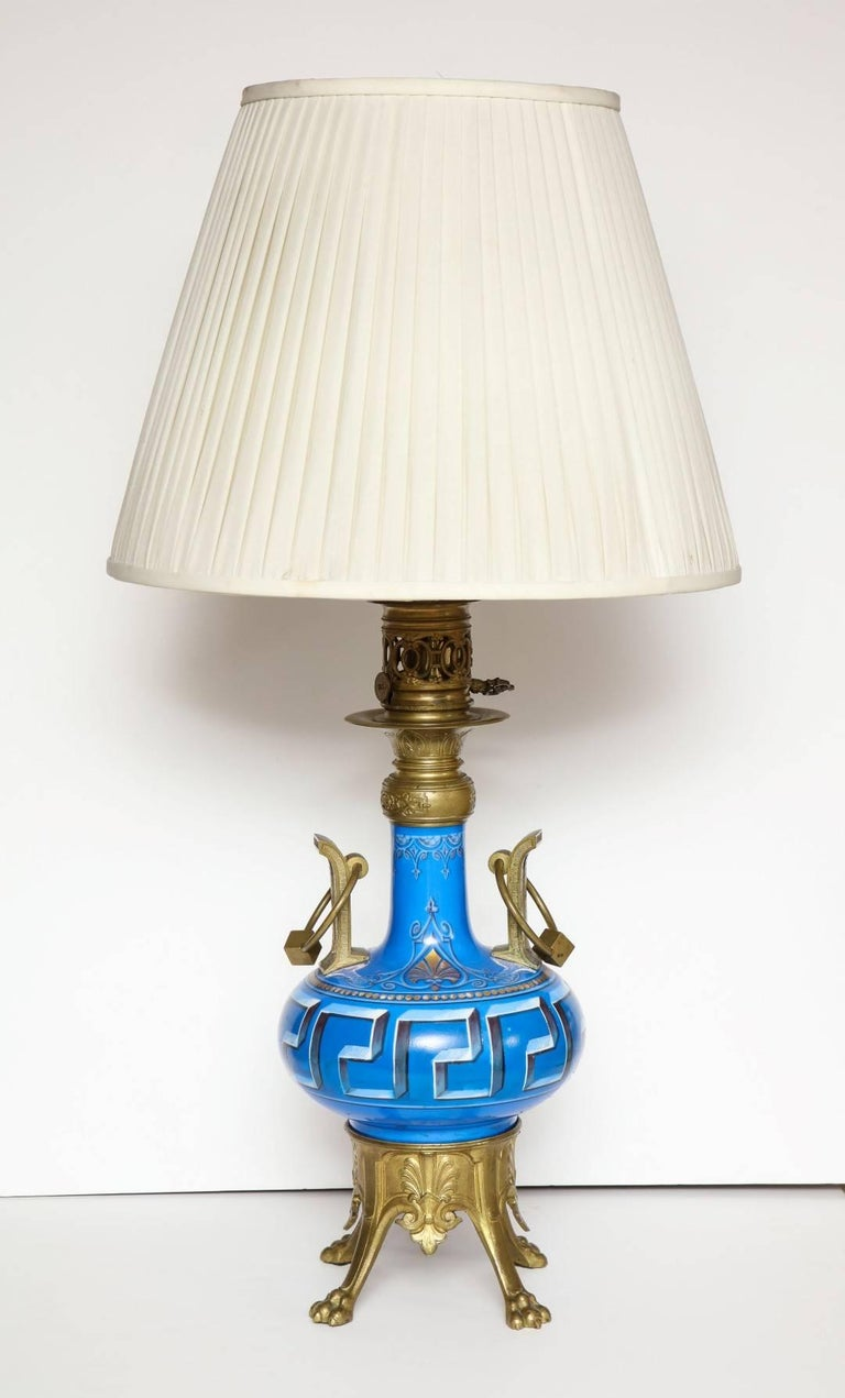 A pair of neo-Grec ormolu-mounted porcelain vases with oil lamp fitting, the ceramic vase with oversized Greek key motif, on platform base with paw feet, wired for electricity.