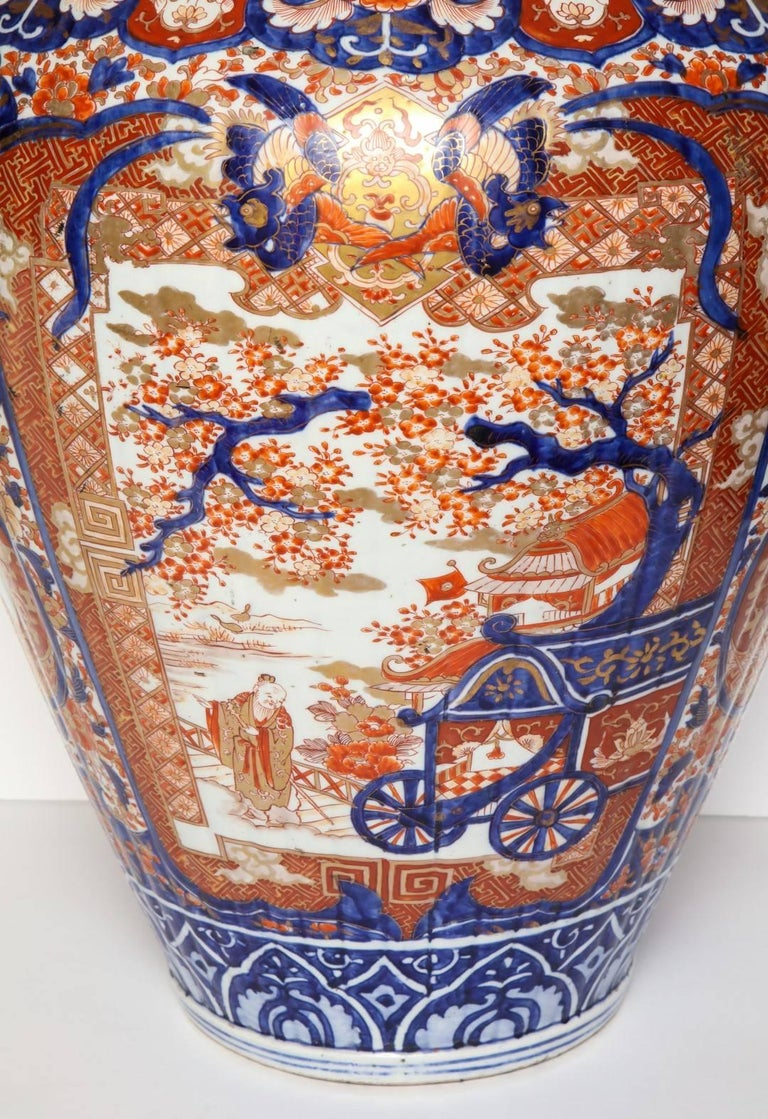 A large Imari jardiniere, decorated with panels depicting aristocratic scenes, bordered with sprays of peony and chrysanthemum, in vibrant iron red, gold and underglaze blue.