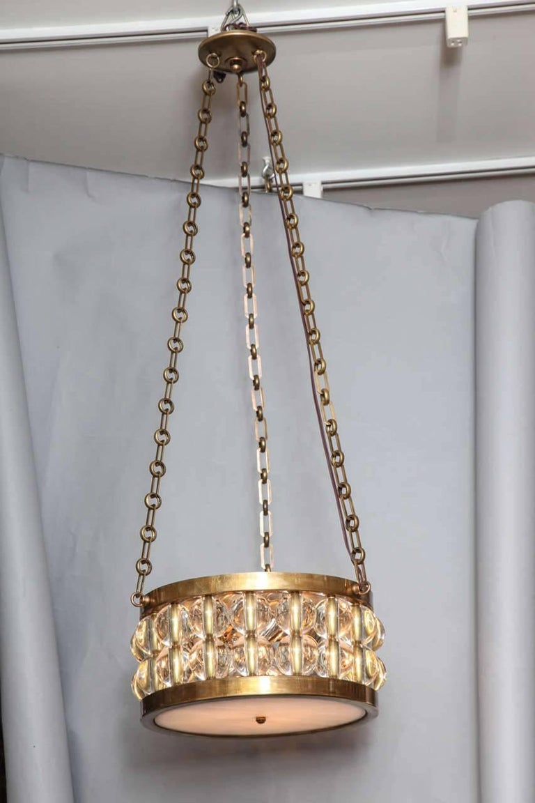 A two-tiered Tambour pendant light, the round polished patinated brass metal frame having two tiers of glass spherical elements suspended from length of bronze chain and canopy, the four light electrical fitting concealed by hand blown opalescent