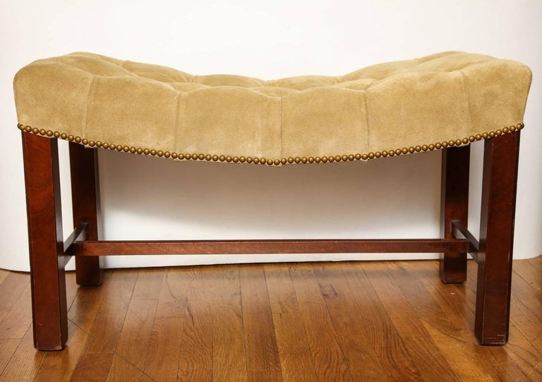 A pair of Chippendale style mahogany benches, suede upholstered saddle seats with nail-head trim.