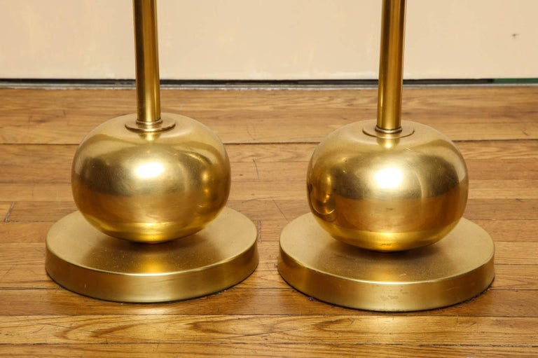 A pair of French Art Deco lacquered brass standing lamps, with Tyrian purple glass prisms, wired for electricity.