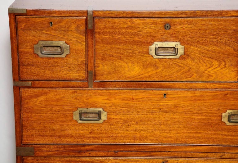 A Victorian mahogany and bois satine brass-mounted Campaign chest, in two parts, the top drawer opening to reveal a shield concealing three satinwood drawers and two compartments, with a gilt-tooled leather inset surface, the bottom area resting on