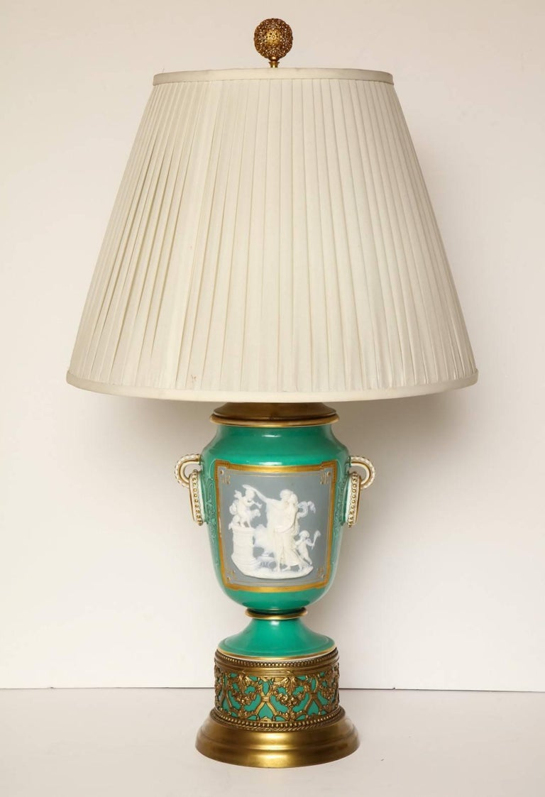 A pair of gilt-brass-mounted pate-sur-pate urns fitted as table lamps, the green ground body depicting gilt-framed reserves of classical scenes with figures in white cameo bas-relief against a blue ground, resting on blind-fret socle on circular