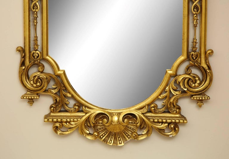 A George II style giltwood mirror in the manner of William Kent, highly architectural and detailed, the arched mirror plate within a cushioned frame centered by profusely carved outer-frame with entrelac sides continuing into foliate scroll