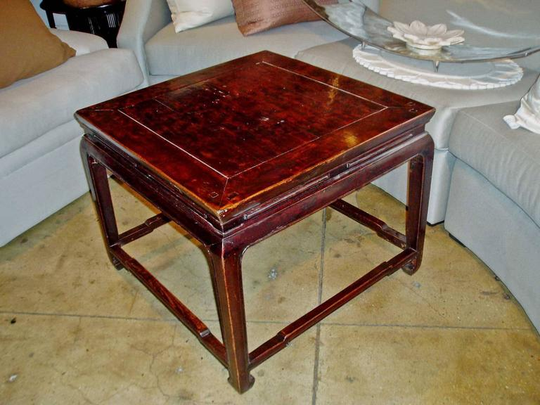 A square coffee table from China, with slotted apron, hoof legs and hump back stretchers.