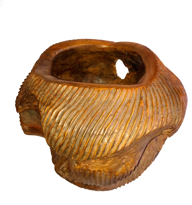 An ornately carved bowl from Indonesia. Hand-carved from a solid piece of Ironwood, this deep bowl exhibits the richness and warmth of the wood texture, combined with an intricate and whimsical carving that makes it a truly original piece.