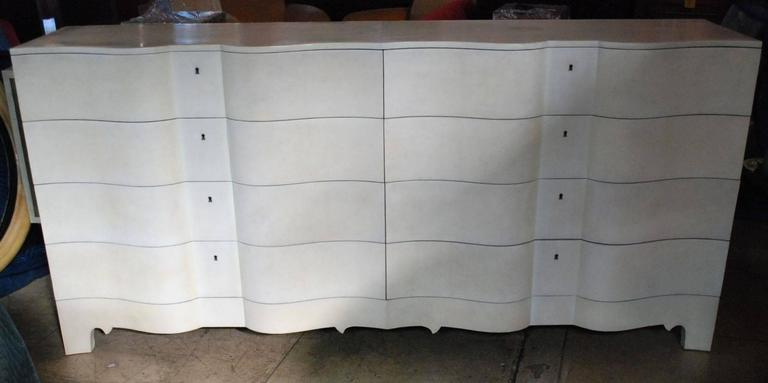 Elegant serpentine front features eight very large drawers cover with natural parchment sideboard.