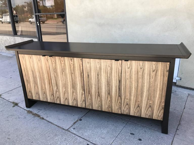 This sideboard is made of ebonized walnut for the body and bleached rosewood for the four doors which open on a shelf on the right and three drawers on the left. Made and stamped by Bernhardt Flair Division.