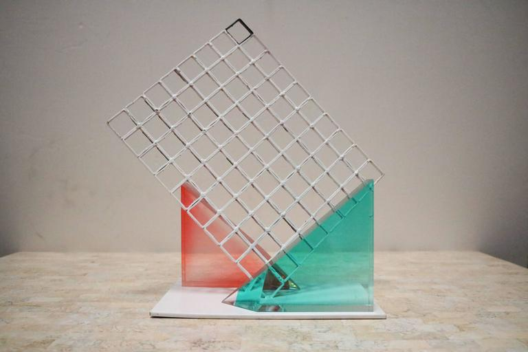 1980s Memphis style sculpture is composed of three pieces. A white metal grid and attached base, and two triangular Lucite pieces that we have arranged on either side. Lucite pieces are not permanently attached and can be moved and used elsewhere as