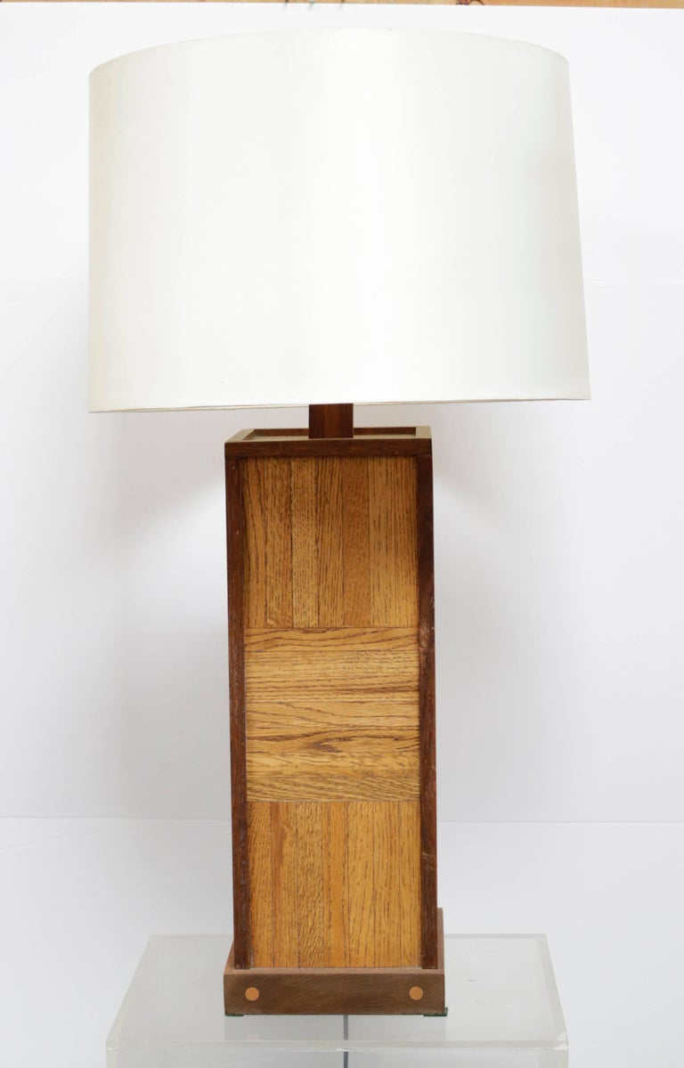 Lamp is made of parquet walnut and has a cylindrical fabric shade.