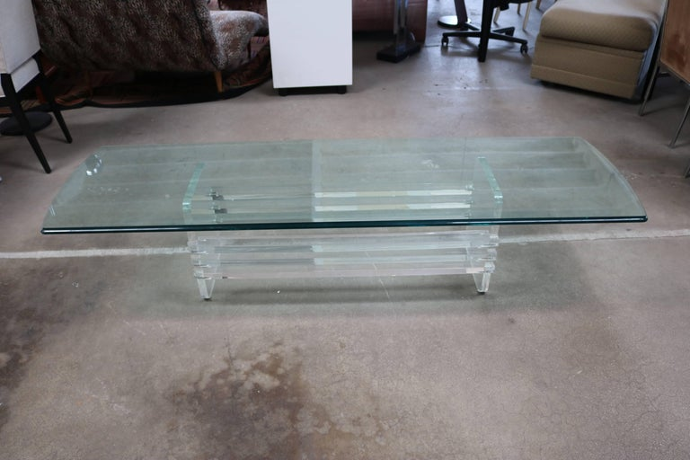 This long coffee table is made up of Lucite slats attached to two end pieces with a long rectangular glass top.
