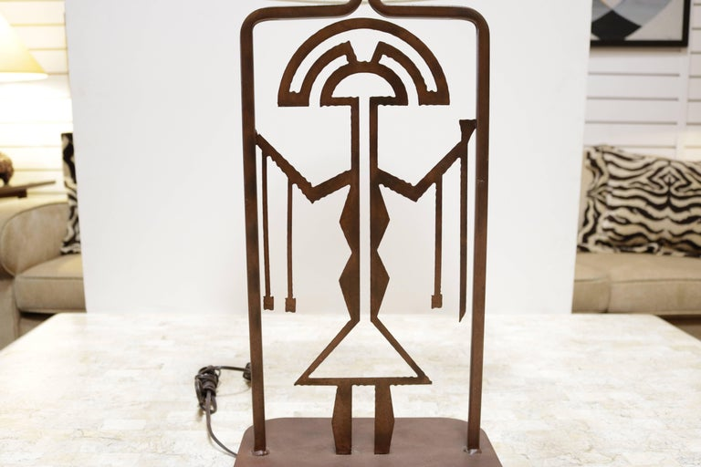 Metal lamp with an intentionally rusted finish. Lamp has a central symbolic figure similar to those used in ancient Latin American art.
