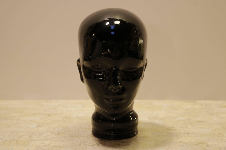 Sculptural black glass head. Hollow with an opening at bottom.