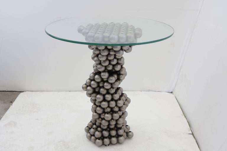 Unusual 1970s gueridon has a base made of chrome steel balls which resembles a spiral or helix. Glass top measures 24