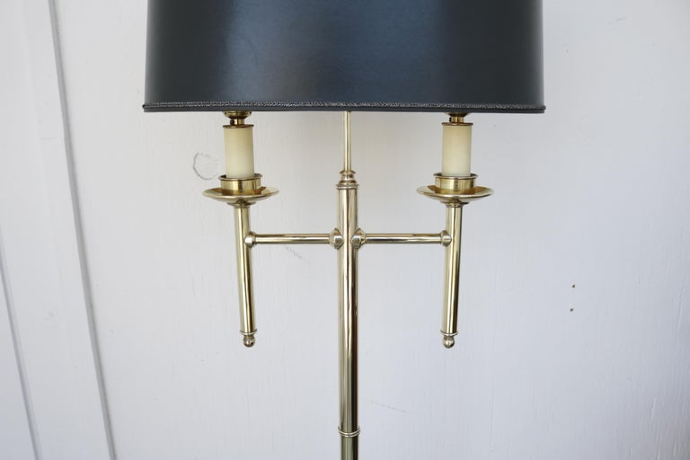 French floor lamp in brass with black ellipse shaped paper shade. Finial has a brass ring design on top. Two sockets.
