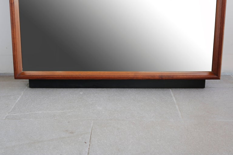1960s standing rectangular walnut framed mirror, with a black stained base, in excellent original condition.