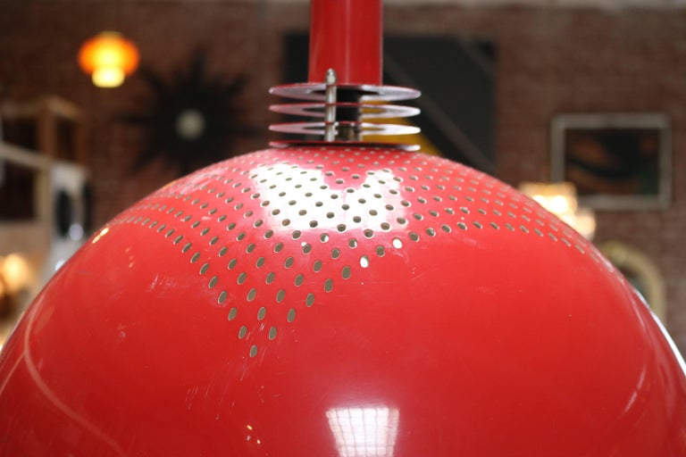 Two vintage large red and white pendants, in the style of Jacobsen. The metal shades are red lacquer on the outside with a perforated design, and white on the inside. Lamps take one bulb each.