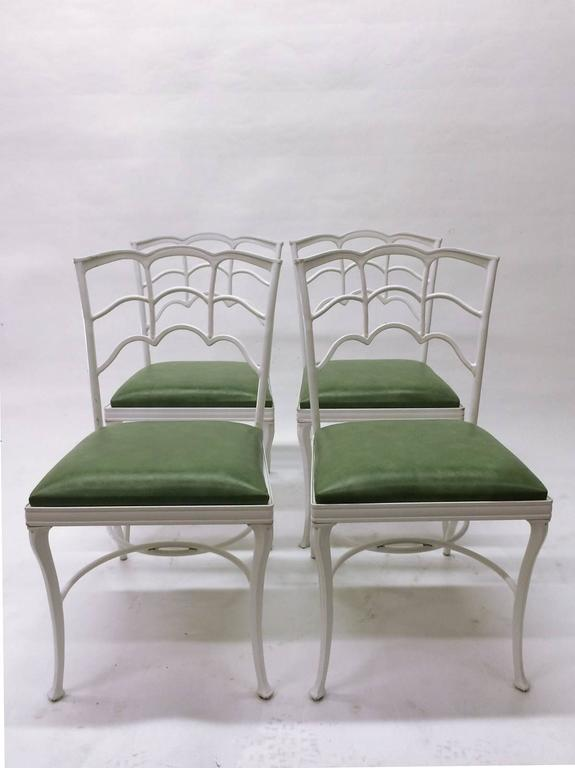 These four outdoor chairs made of cast iron,are strong and sturdy and powder coated in white.  The green vinyl cushions are comfortable, clean and original.