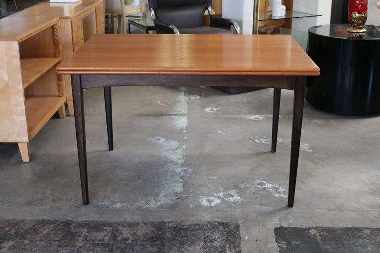 This expandable dining table with flip-top is made of teak and features brass hinges. The legs have been stained in dark brown which gives it a weightless look as if the top was floating.