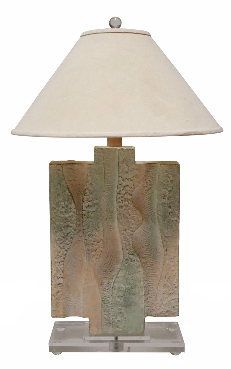 Pair of 1980s ceramic table lamps with an artful, textured finish and pastel tones. Each sits on a Lucite base and has it's original canvas shade.