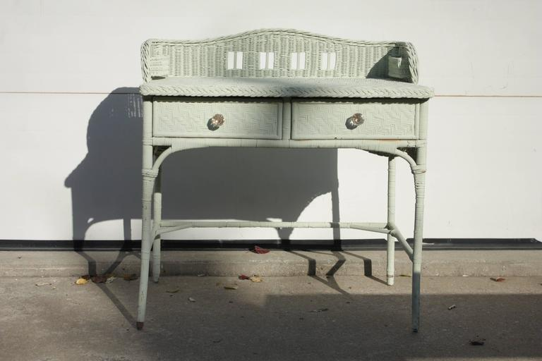 Vintage English Mint Seafoam Painted 1930s Writing Table Desk with two drawers, narrow legs and decorative cross support. Decorative clear pulls, cut-out camelback-style backsplash with functional and decorative single pocket fixed side baskets or