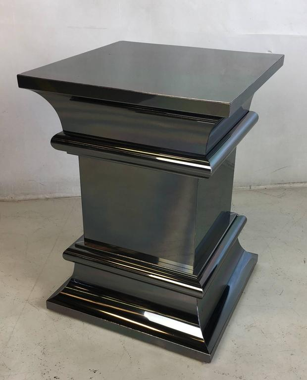 Unique and finely crafted pair of column-form side tables or pedestals. The metal forms are attached to a heavy wood substrate.
