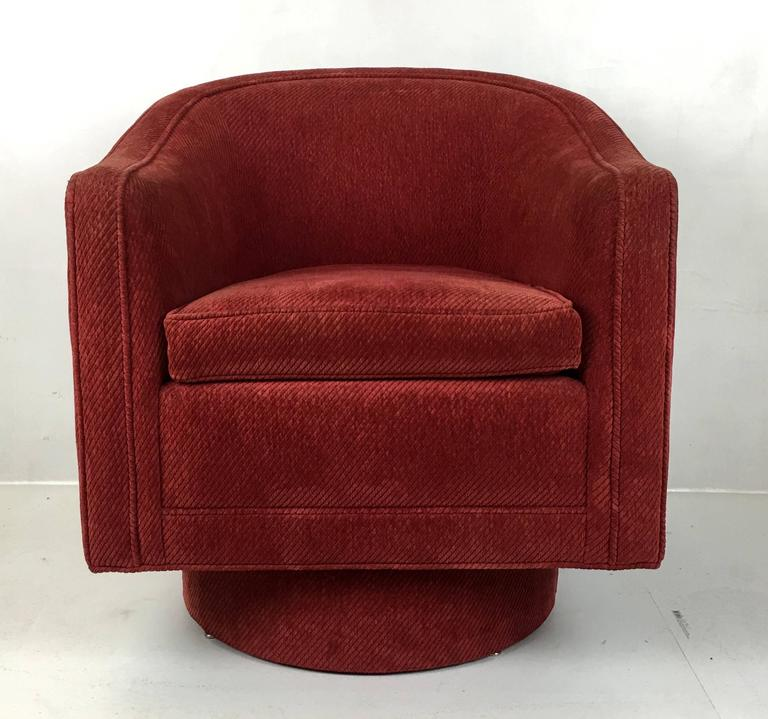 Classic Milo Baughman swivel chair by Milo Baughman. The chair is raised on a tall drum base. The chair is very comfortable.