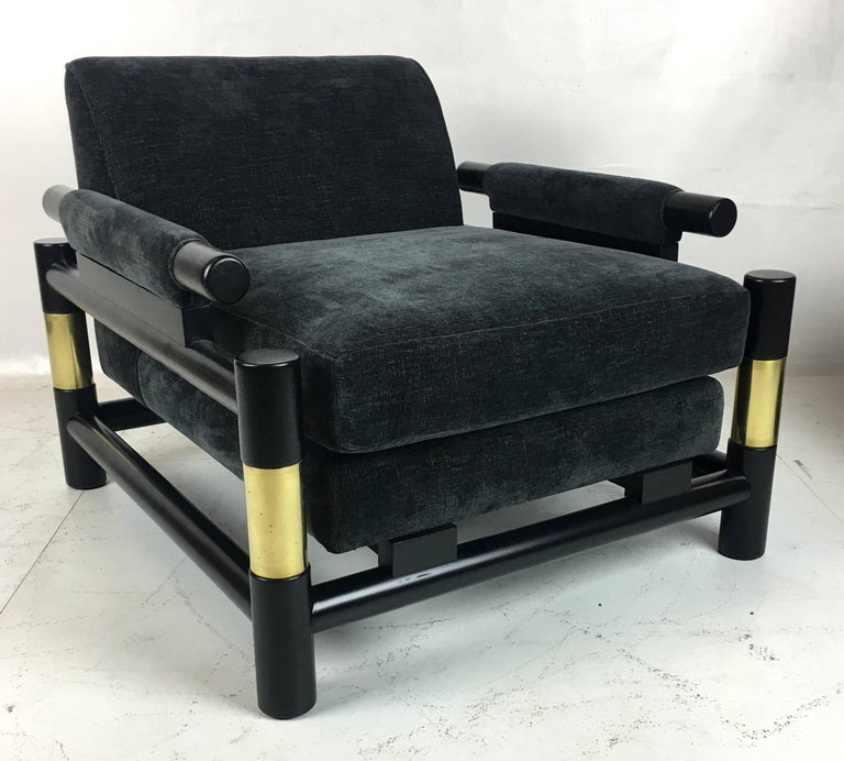 Striking pair of ebonized open frame lounge chairs in the style of Paul Laszlo. The pair have been painstakingly restored; refinished, brass polished, and reupholstered in luxurious charcoal grey chenille. Highest quality materials and workmanship