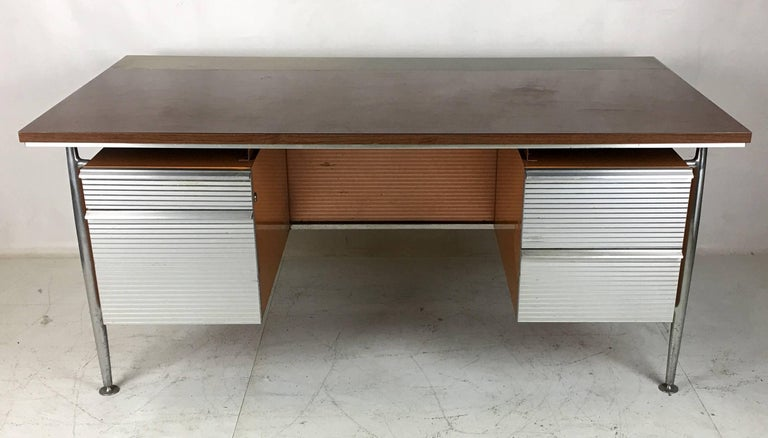 Aluminum and steel executive desk by the noted architect Welton Becket for his modernist icon that is the Kaiser Aluminum headquarters in Oakland, CA. The desk is in very good original condition. The top is wood-grain laminate with an aluminium