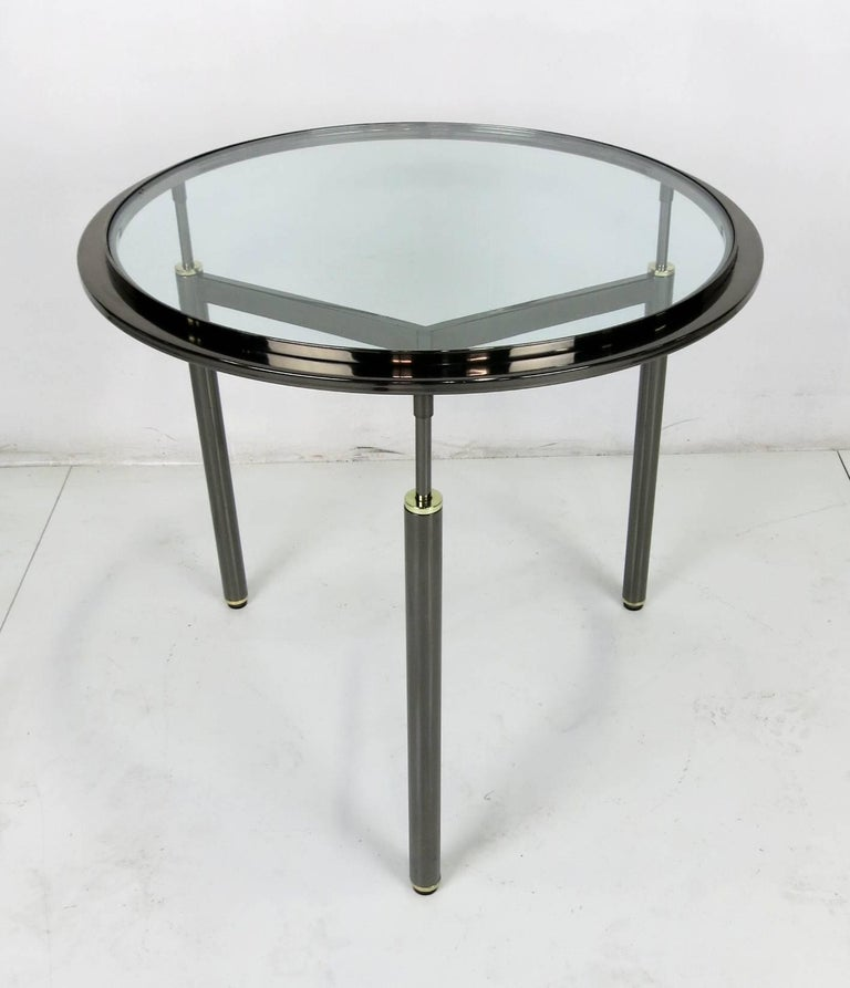 Handsome pair of gunmetal plated tripod tables with brass mounts in the style of John Saladino.