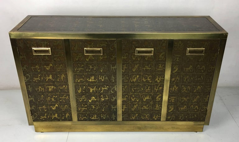Rare brass clad two-door cabinet decorated with etched abstract figures by Bernard Rohne for Mastercraft. The etched design is featured on three sides and the top of the cabinet. This versatile statement piece would make an excellent Buffet,