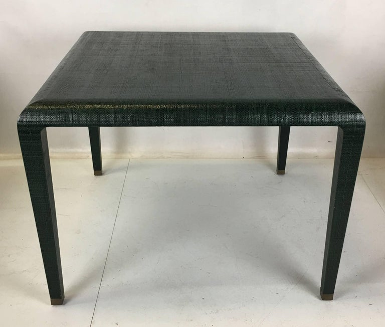 Superbly crafted games table clad in lacquered Raffia with two pencil drawers on one side. The tapered square legs terminate in heavy brass sabots. The Raffia is lacquered in hunter green with black undertones. Van Horn's quality and workmanship is