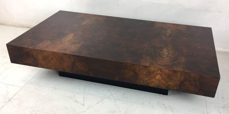 Handsome Burl Veneer coffee table raised on a black Plinth base. The table has been meticulously restored in open grain lacquer. The grain on this table is spectacular and the refinish has really brought out the brilliance of the materials.