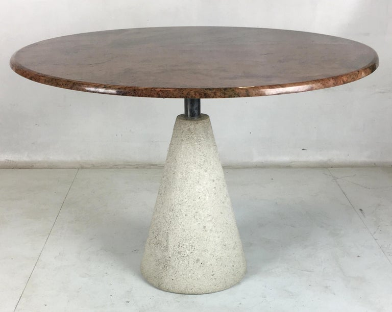 Modernist dining table consisting of a rough concrete inverted cone base with a polished stainless steel neck supporting a beautifully figured granite top. This table is a stunning modern statement piece.