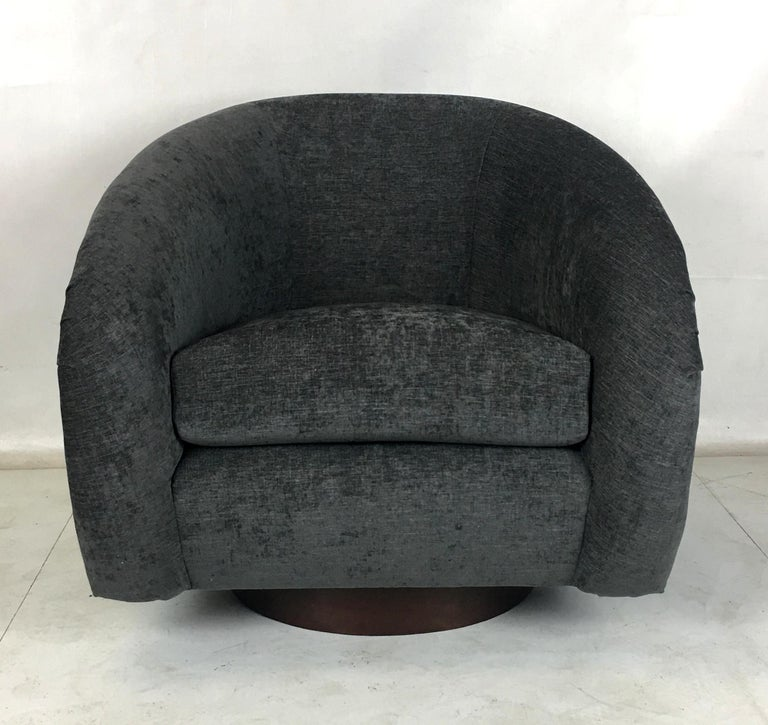 Pair of Milo Baughman roll arm swivel chairs raised on walnut veneer circular bases. The pair have been freshly upholstered in charcoal gray tweed upholstery. The bases have been refinished with new swivel plates. These chairs are luxuriously