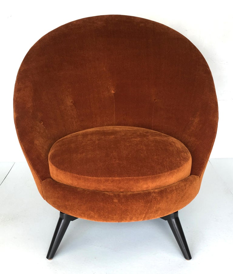 Swivel egg chairs in the style of Jean Royère. This sophisticated chair has been freshly upholstered in heavy-weight, backed burnt gold velvet. These super stylish and versatile chairs are as comfortable as they look. Dacron and foam over webbed and