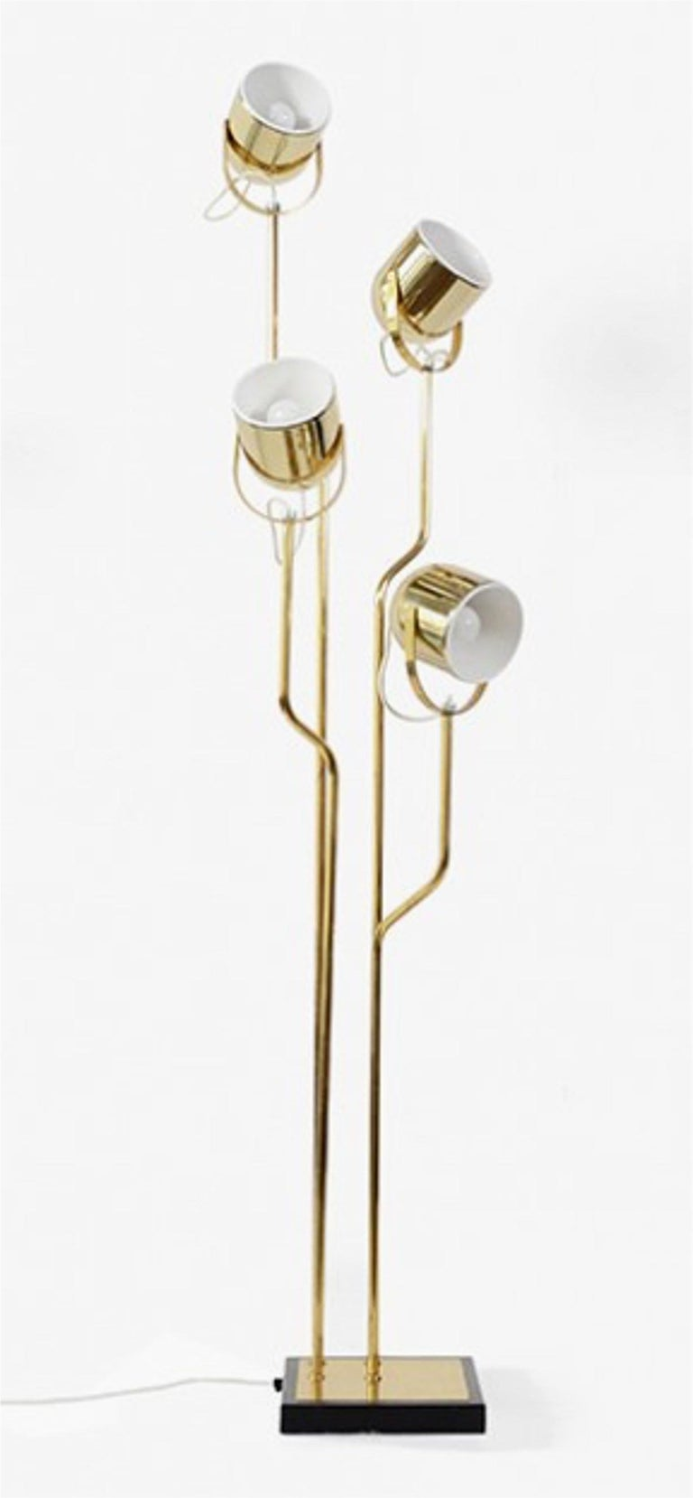 Four-arm adjustable head floor lamp in brass by Reggiani-Italy.  Enameled cast iron base with brass cover trim.