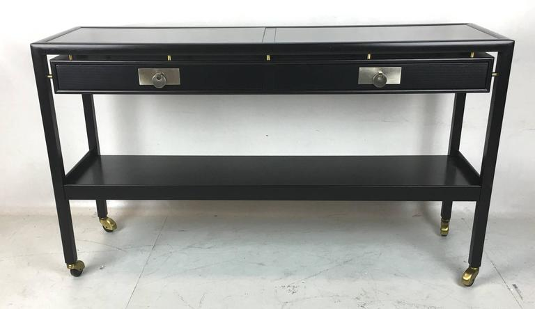 Handsome rolling server table with two suspended drawers and undershelf with brass hooded casters. This piece would make a perfect dry bar with its black inset Micarta top and accessory drawers, as well as a galleried glass storage shelf. A very