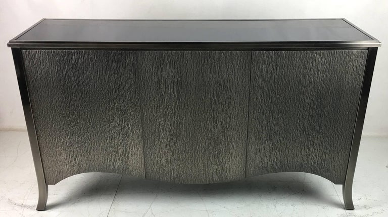 Textured Steel clad cabinet with steel cabriole legs by Mastercraft. The three-door buffet has an inset black glass top and adjustable height interior shelves. The door fronts and sides are clad in heavy-gauge embossed steel. Top quality