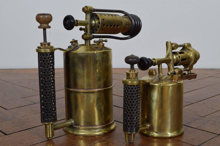 Each in excellent condition consisting of a vessel for storing oil, a pump, a valve for adjusting flame, and a perforated steel handle, the smaller dimensions: height 7.75, depth 4, length 11.