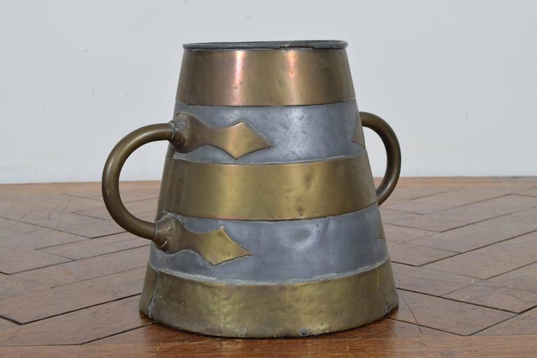 Of tapering form with side handles, with pewter and brass decoration.