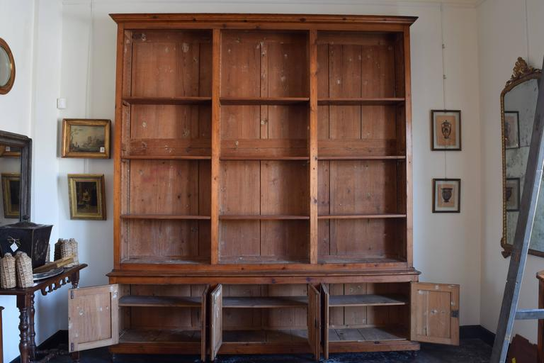 """The large bookcase having stepped back upper section with adjustable shelving and a lower section with three sets of paneled doors, raised on turned feet.   Width of body 111.5"""" and cornice is 114.5"""", height of bottom section is"""
