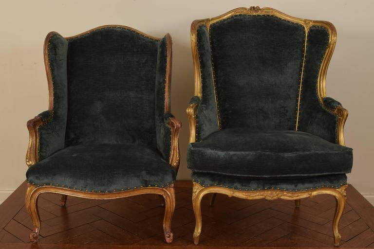 Measurements are for larger chair, the two chairs having arched backrests and shaped wings, the larger with a down filled cushion, the smaller chair: Height 42.5. SH 16. Length 31. Depth 23.