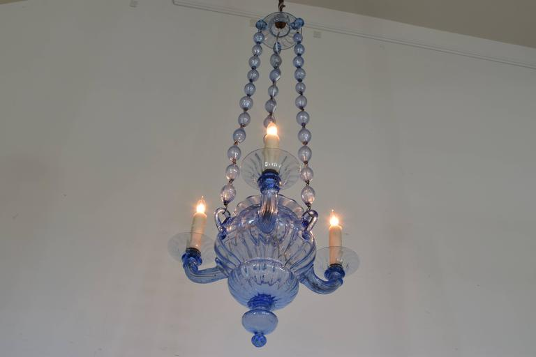 Having a glass canopy and hanging from blown glass large bead chains, the urn shaped body with a removable finial issuing three arms.  UL listed/wired.