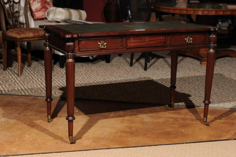 A lovely reproduction writing table with gilt tooled leather top and scalloped rounded corners. Three faux drawers on the back and three functional drawers on the front (all with brass pulls) lets it float in a room. Legs are reeded and fluted