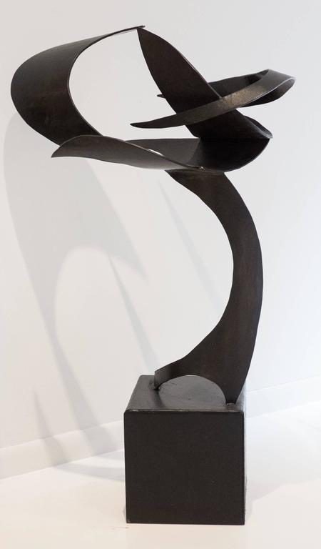 Fluidly abstract, floor-standing sculpture of patinated steel, perched on attached cubic steel base. Titled